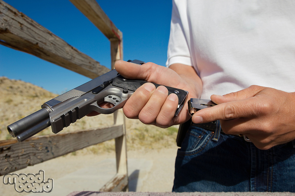 Man loading magazine into gun at firing range, close-up