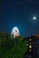 Chartres, France. View across town of the brightly lit Ferris wheel at night against the backdrop of a glowing moon and stars.