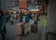 Chinese or Taiwanese traveler burdend with packages heads to the airport bus in Shinjuku, Tokyo, Japan.<br />  <br /> Relaxed visa requirements for Chinese travelers and a weak Japanese Yen have attracted so-called, &quot;bakugai&quot; (explosive buyers) to Japan.  Reuters reports that Chinese shoppers in Japan spend on average US$ 2,300/ person.  That is 75% more than other tourists spend.