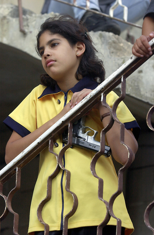 A young Palestinian girl  holds a handgun as she watches gunmen march down the street at  the Aida refugee camp celebrating the Israeli pull out from the West Bank town of Beit Jalla Thursday Aug. 30, 2001.