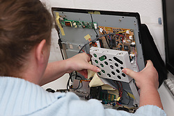 Woman with a mild learning disability working as a trainee computer technician, shown here changing hard drive,helped into employment by the Ready 4 Work team, Nottinghamshire County Council