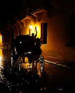 A horse drawn carriage passes along one of Cartagena's narrow, cobblestone streets.