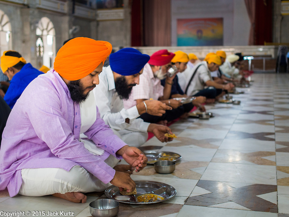 """08 FEBRUARY 2015  BANGKOK, THAILAND:  Sikh men eat breakfast during the community meal at the Sikh temple in Bangkok. Thailand has a small but influential Sikh community. Sikhs started coming to Thailand, then Siam, in the 1890s. There are now several thousand Thai-Indian Sikh families. The Sikh temple in Bangkok, Gurdwara Siri Guru Singh Sabha, was established in 1913. The current building, adjacent to the original Gurdwara (""""Gateway to the Guru""""), was built in 1979. The Sikh community serves a daily free vegetarian meal at the Gurdwara that is available to people of any faith and background.   PHOTO BY JACK KURTZ"""