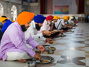 "08 FEBRUARY 2015  BANGKOK, THAILAND:  Sikh men eat breakfast during the community meal at the Sikh temple in Bangkok. Thailand has a small but influential Sikh community. Sikhs started coming to Thailand, then Siam, in the 1890s. There are now several thousand Thai-Indian Sikh families. The Sikh temple in Bangkok, Gurdwara Siri Guru Singh Sabha, was established in 1913. The current building, adjacent to the original Gurdwara (""Gateway to the Guru""), was built in 1979. The Sikh community serves a daily free vegetarian meal at the Gurdwara that is available to people of any faith and background.   PHOTO BY JACK KURTZ"