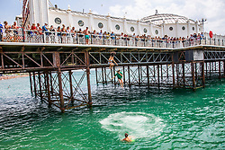 © Licensed to London News Pictures. 01/07/2016. Brighton, UK. A group of friends can be seen jumping of the Brighton Palace Pier during another hot say on the south coast of England. Photo credit: Hugo Michiels/LNP