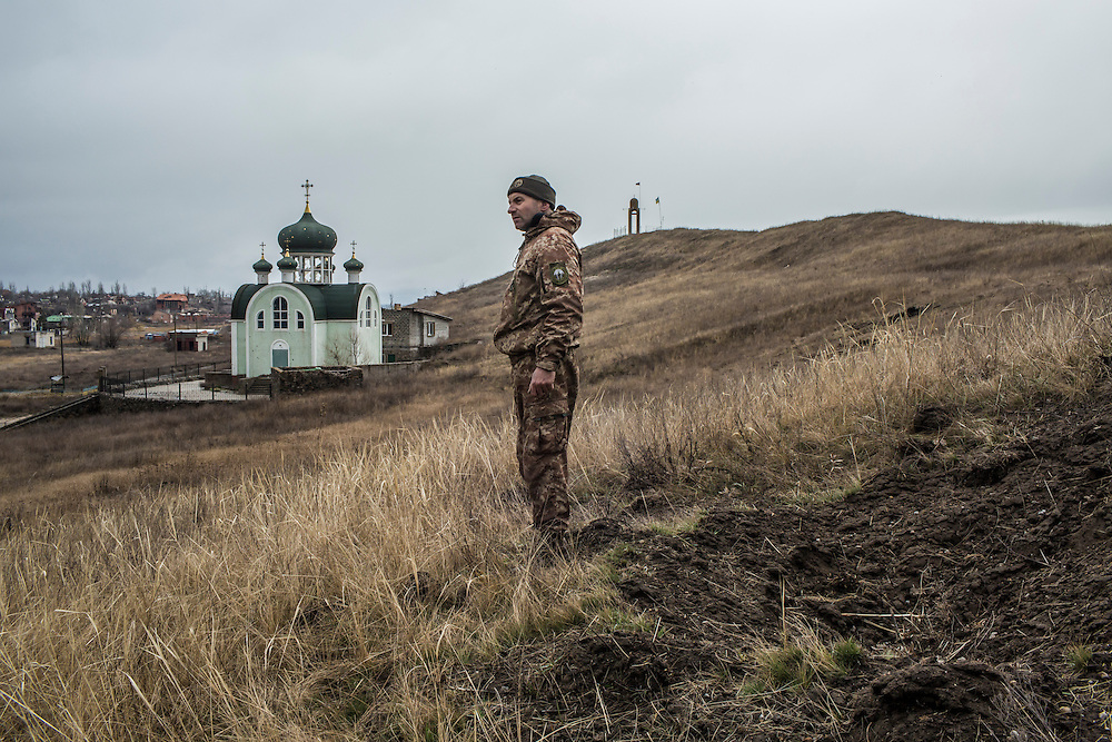 A Ukrainian soldier stands next to a crater left by shells launched the previous day by pro-Russian rebels on Saturday, March 19, 2016 in Shyrokyne, Ukraine. The area was until recently the scene of intense fighting, but is now controlled by Ukrainian forces.