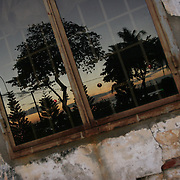 """The waterfront is reflected in the window of a French colonial house in Vung Tau, Vietnam, a popular beach resort a few hours' drive from Ho Chi Minh City. Former glam rock star Gary Glitter is currently behind bars in the resort town, facing charges of child molestation. Glitter, whose real name is Paul Gadd, was convicted in Britain in 1999 of possessing child pornography and served two months in jail. In 2002 he was kicked out of Cambodia, a country with lax regulation of prostitution. Glitter's 1970's hit """"Rock and Roll (Part 2)""""  is played regularly at sporting events throughout North America and Europe."""