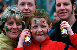 IRELAND DUBLIN 17MAR00 - Paul Caffrey (12, C), and his mother Pauline (L) pose with spray cans on O'Connell Bridge during Dublin's St. Patrick's Day celebrations. He and his mother earn an income from colouring hair and faces of passers-by (rear) who long for some extra decoration...jre/Photo by Jiri Rezac..© Jiri Rezac 2000..Contact: +44 (0) 7050 110 417.Mobile:  +44 (0) 7801 337 683.Office:  +44 (0) 20 8968 9635..Email:   jiri@jirirezac.com.Web:     www.jirirezac.com..© All images Jiri Rezac 2000 - All rights reserved.