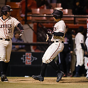 24 February 2018: The San Diego State Aztec baseball team competes in day two of the Tony Gwynn legacy tournament against #4 Arkansas. San Diego State Aztecs infielder Jordan Verdon (21) congratulates teammate Chase Calabuig (34) after he scored in the bottom of the sixth inning to tie the game at 2-2. The Aztecs dropped a close game to the Razorbacks 4-2. <br /> More game action at sdsuaztecphotos.com