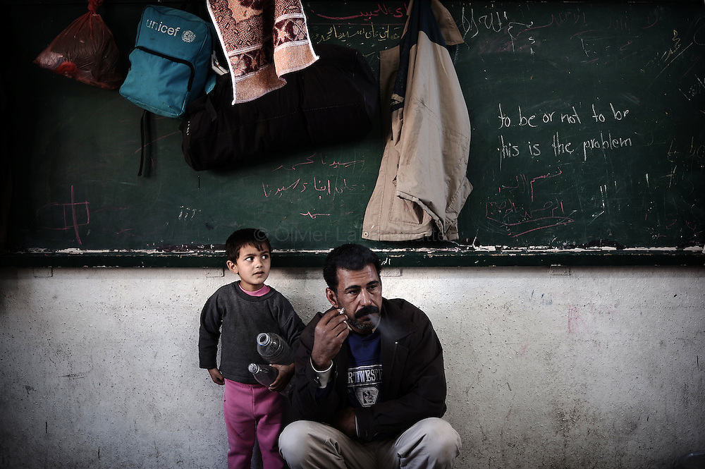 A Palestinian refugee man smokes a cigarette as he rests with his son at a school run by UNRWA, the UN agency for Palestinian refugees, in Gaza City on January 22, 2009. The United Nations urged Israel to reopen Gaza crossings as senior officials assessed war damage and the Jewish state warned it would strike again if Hamas rearms through smuggling tunnels.