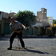 A rebel fighter shoots at pro-Gaddafi snippers during the third day of street-to-street battle for control of the strategically coastal city of Zawiyah.