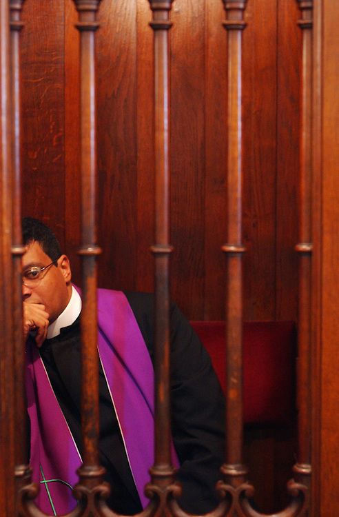 """Father Miguel Vargas listens to confession on """"Miercoles Santa""""(Holy Wednesday) during Holy Week at the Santa Teresa church."""