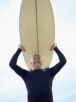 Senior man carrying surfboard on head (low angle view)