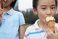 Boy and girl (7-9) eating ice cream close-up (cropped)