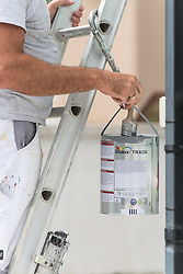 A painter and decorator works on a house.