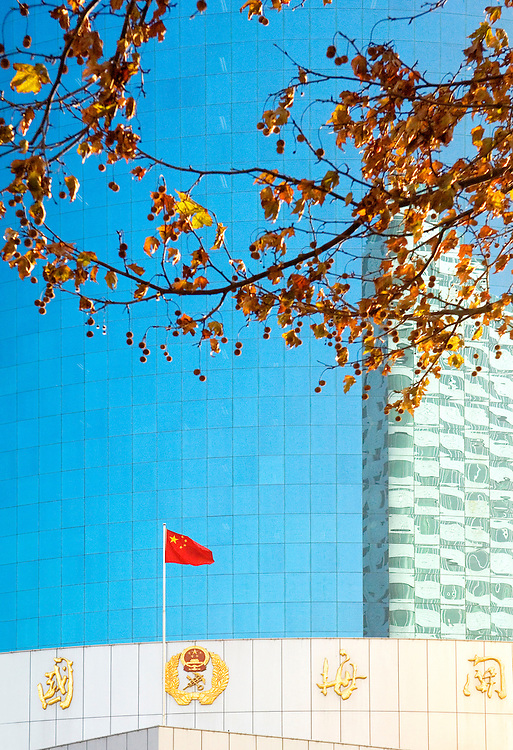 Chinese flag and reflective glass of new port authority Customs Building in the city centre, Yantai, Shandong Province, China