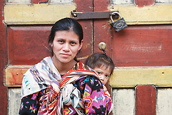 Woman with child on back in colorful doorway, Chichicastenango, Guatemala
