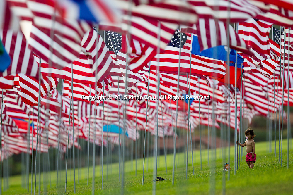 A boy stands amongst 3,000 US flags are displayed at Pepperdine University to mark the 14th anniversary of the 9/11 terror attack, September 10, 2015 in Malibu, California.  Photo by Ringo Chiu/PHOTOFORMULA.com)