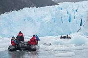 Expedition travelers aboard zodiac inflatable boats explore Garibaldi glacier national park in Parque Nacional Alberto de Agostini, Chile.