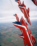Seen from the cockpit of another Hawk of the elite 'Red Arrows', Britain's Royal Air Force aerobatic team during an In-Season Practice (ISP) training flight near their base at RAF Scampton. Seen through the explosive Plexiglass cockpit of a tenth plane, we look sideways towards other pilots diving downwards as they their machines after a loop, their organic white smoke pouring from their jet pipes to emphasize their paths through the air. In front of a local crowd at the airfield the team work their way through a 25-minute series of display manoeuvres that are loved by thousands at summer air shows. After some time off, spare days like this are used to hone their manual aerobatic and piloting skills before re-joining the air show circuit. Since 1965 they've flown over 4,000 shows in 52 countries.