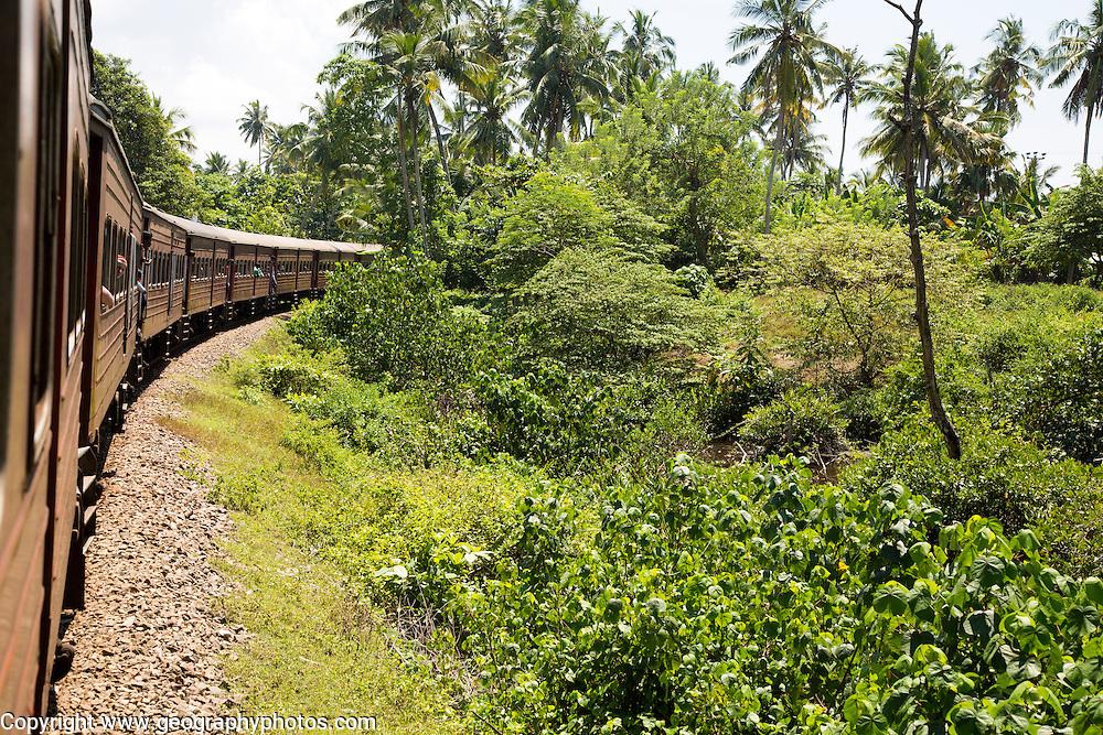 Railway train passing through countryside between Galle and Mirissa, Sri Lanka, Asia