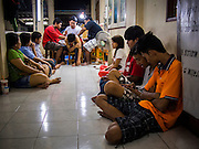 "14 MARCH 2014 - NAKHON CHAI SI, NAKHON PATHOM, THAILAND: People wait to get tattooed while an archan gives a man a sak yant tattoo at Wat Bang Phra. Wat Bang Phra is the best known ""Sak Yant"" tattoo temple in Thailand. It's located in Nakhon Pathom province, about 40 miles from Bangkok. The tattoos are given with hollow stainless steel needles and are thought to possess magical powers of protection. The tattoos, which are given by Buddhist monks, are popular with soldiers, policeman and gangsters, people who generally live in harm's way. The tattoo must be activated to remain powerful and the annual Wai Khru Ceremony (tattoo festival) at the temple draws thousands of devotees who come to the temple to activate or renew the tattoos. People go into trance like states and then assume the personality of their tattoo, so people with tiger tattoos assume the personality of a tiger, people with monkey tattoos take on the personality of a monkey and so on. In recent years the tattoo festival has become popular with tourists who make the trip to Nakorn Pathom province to see a side of ""exotic"" Thailand.  PHOTO BY JACK KURTZ"