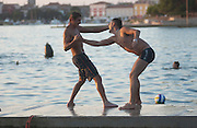 Badevergnügen in der Bucht vor Porec. Zwei junge Männer rangeln auf der Kaimauer versuchen sich gegenseitig ins Wasser zu werfen. | Two young men playfully establish a rank order on a pier and try to shove each other into the water.