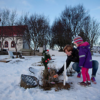 Mother and daughter memorialize the dead by lighting a candle at their loved ones' grave on Christimas at Kotstrandarkirkja, Iceland, December 24, 2013.