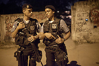 Police Pacification Unit (UPP) officer XXX Pinheiro, right, with an officer, patrols the streets in Complexo do Caju, a complex of a newly pacified favelas in the North Zone, Rio de Janeiro, Brazil, on Saturday, April 27, 2013. <br />