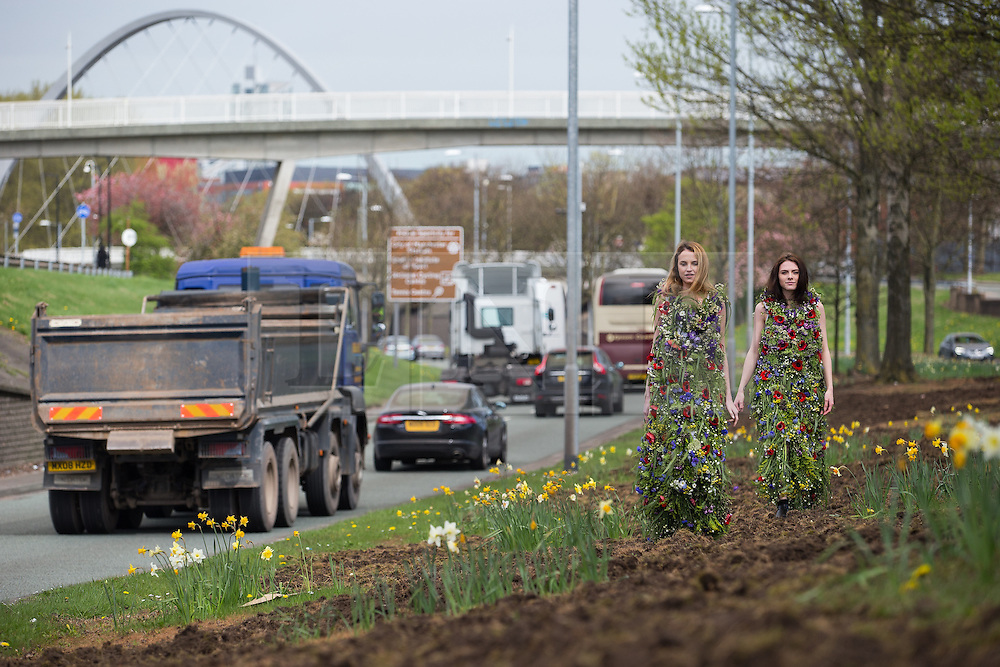 """© Licensed to London News Pictures . FREE TO USE PHOTOGRAPH . No syndication , onward sale of transfer permitted . 16/04/2015 . Manchester , UK . As England bathes in warm Spring sunshine , models Danielle Bowers (21 from Liverpool) and Ailyce Ridings (correct, 20, from Manchester) model wild flower dresses on Manchester's Princess Parkway (A5103) to mark Grow Wild's England flagship project , """" Tale of Two Cities """" , a joint venture between rival cities Manchester and Liverpool , which will see heavily travelled urban landscapes transformed in to stunning wildflower meadows . Photo credit : Joel Goodman/LNP"""