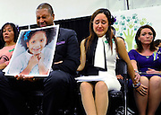 Jimmy Greene, foreground left, Nelba Marquez-Greene, center, parents of Sandy Hook Elementary School shooting victim Ana Marquez-Greene, and Nicole Hockley, right, mother of victim Dylan Hockley, react during a news conference at Edmond Town Hall in Newtown, Conn., Monday, Jan. 14, 2013. One month after the mass shooting at the school, the parents joined a grassroots initiative called Sandy Hook Promise to support solutions for a safer community. (AP Photo/Jessica Hill)