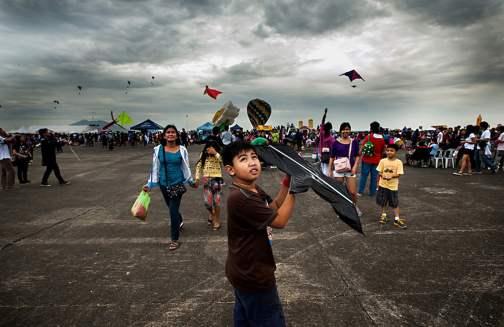 A boy launches a kite at the 2012 Clark, Philippines Hot Air Balloon Festival/Air Show