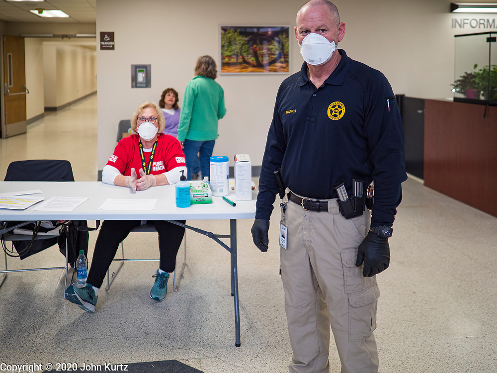 """18 MARCH 2020 - DES MOINES, IOWA: JOLYN CATALDO, a RN with the Polk County Department of Public Health, (left) and Security Officer BRASWELL wait for people to come into the Polk County offices in downtown Des Moines. They screened them before directing them to the proper office. The county reduced its services available to the public in order to reduce the number of people coming into county buildings. County workers are screening people coming into the building, asking about recent travel and health. On Wednesday morning, 18 March, Iowa reported 29 confirmed cases of the Coronavirus. Restaurants, bars, movie theaters, places that draw crowds are closed for at least 30 days. There are no """"shelter in place"""" orders in effect anywhere in Iowa but people are being encouraged to practice """"social distancing"""" and many businesses are requiring or encouraging employees to telecommute.      PHOTO BY JACK KURTZ"""