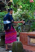Old Balinese woman praying as she enters a temple in Sukawati, Bali, Indonesia