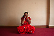 A Nepalese woman sits on the floor and covers her face with her hands in the Voice of Children centre in Kankeshori area of Kathmandu, Nepal.  Her 6-year old daughter has been sexually abused and she is receiving counseling and support from Voice of Children charity.  The not-for-profit organisation supports street children and those who are at risk of sexual abuse through educational and vocational training opportunities, health services and psychosocial counseling.