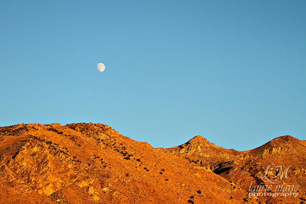 Moon at sunset over Cali desert mountains