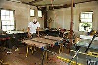 Andy Bauer in the workshop at Riverbank House building tables out of black walnut on Tuesday afternoon.  (Karen Bobotas/for the Laconia Daily Sun)