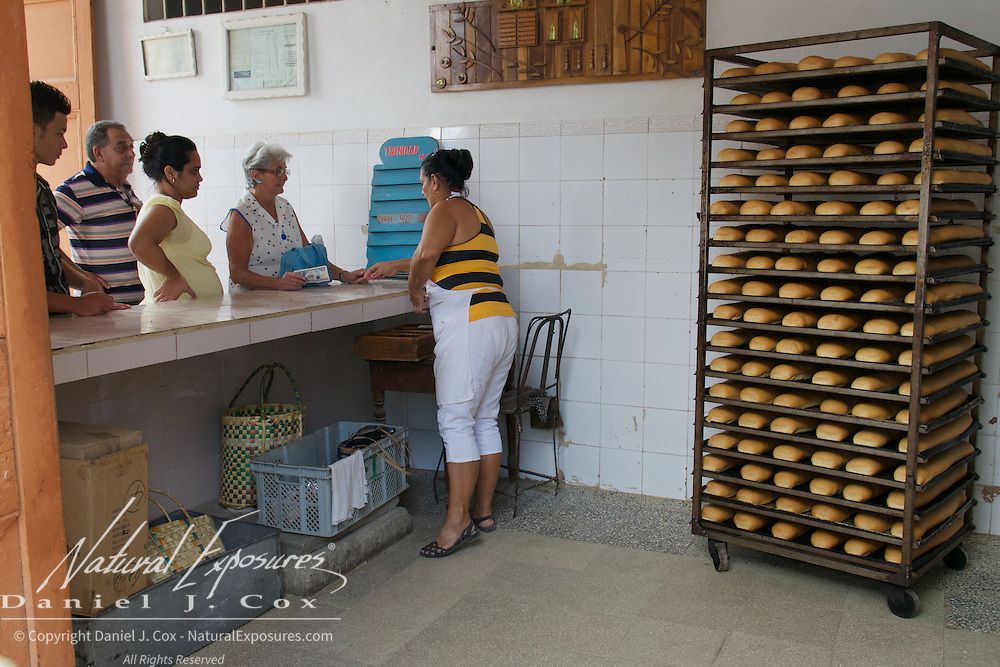 A woman hands out fresh bread at one of Trinidad's many Food Ration stores. Cuba.