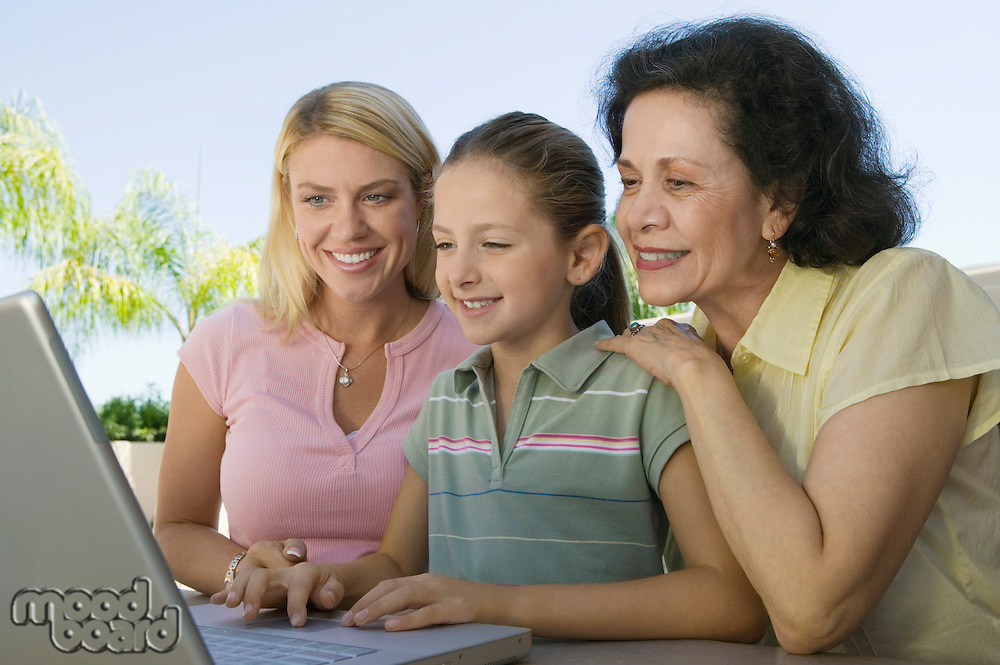 Grandmother and Mother Watching Girl Using Laptop