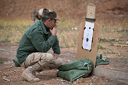 © Licensed to London News Pictures. 30/03/2015. Erbil, Iraq. A Kurdish peshmerga fighter inspects his target on firing range after zeroing his rifle during a training package run by coalition forces instructors at a military training area near Erbil, Iraq.<br /> <br /> The training is part of a four week long package, the first to be held with a complete peshmerga battalion, run by coalition forces mobile training teams (MTT) in Kurdistan with the aim to make the peshmerga more efficient in combatting the Islamic State. Photo credit: Matt Cetti-Roberts/LNP