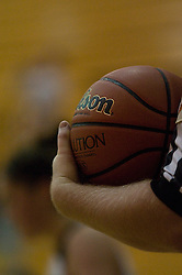 Basketball official holds basketball before out-of-bounds play.