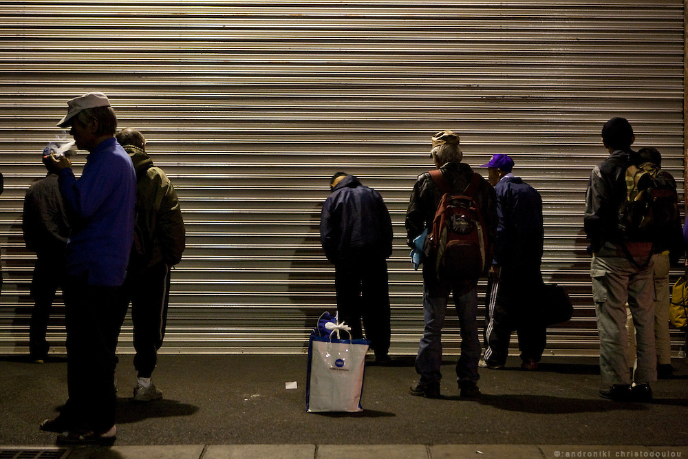 Day laborers waiting outside Airin Labor Welfare Center's shatters to open at 5 am and the dayly job hunting to begin. They hope to get picket up by contractors offering work or to get some of the few jobs offered by the Lador Welfare Center. The ones who don't get a job and are homeless,  just stay inside the building using it as a temporary shelter..The old name of the area now called Airin, was untill 1966 Kamagasaki and many people still call it like that. .Kamagasaki (????) is an old place name for a part of Nishinari-ku in Osaka, Japan. Airin-chiku (???????) became the region's official name in May, 1966.Sections of four different towns: Nishinari-ku Taishi (??????), Haginochaya (?????), Sanou (???), North Hanazono (????) and Tengachaya (?????) are collectively known as the Kamagasaki region..Kamagasaki as a place name existed until 1922. Kamagasaki is known as Japan's largest slum, and has the largest day laborer concentration in the entire country. 30,000 people are estimated to live in every 2,000 meter radius within this region. An accurate count of occupants has never been produced, even in the national census, due to the large population of day laborers who lack permanent addresses..