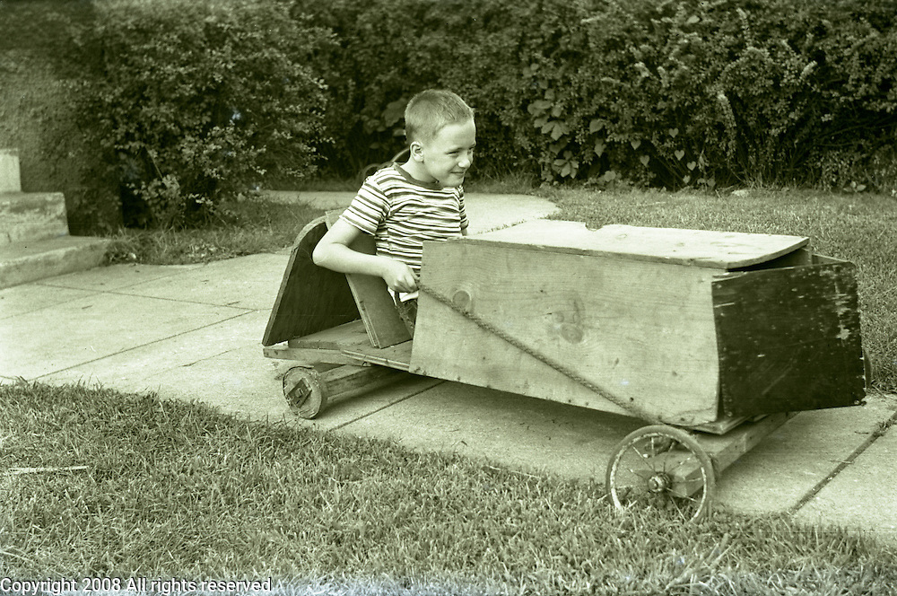 A young boy poses for a photo in his wooden soapbox car which utilizes lawnmower wheels during the 1950s or 1950s.