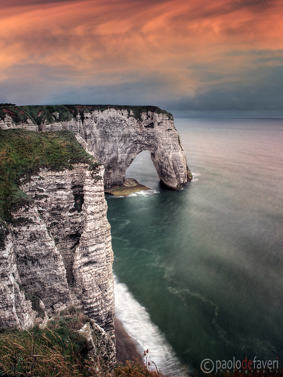 "A moody representation of the cliff known as La Manneporte, which is part of the amazing rocky coast around Etretat in Upper Normandy, France, altogether known as Les Failases d'Etretat..La Manneporte, which in French means ""the great door"" is one of the most beloved subject of the famous French impressionist painter Claude Monet, who depicted it in more of 40 paints..Monet loved very much Etretat and its cliffs, and settled here his house and atelier for years.."