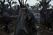 A woman wears a plastic trash bag over her while standing in an olive tree grove outside the Moria registration camp on the island of Lesvos, Greece on October 21, 2015. Days of rain worsened already poor conditions for those waiting to be registered. A river formed where people had been sitting in line and several people were taken to a NGO medical facility a few kilometers away after losing consciousness. Asylum seekers who arrived on Lesvos by sea from Turkey are required to be registered and approved to travel by Greek police before leaving the island. In October and November, over 300,000 thousand asylum seekers were registered at Moria and other hotspots on Lesvos in 2015. Most waited for up to a week, sleeping on the group with limited access to food, water and no bathrooms, in a line that stretched for over a kilometer to be registered at Moria.