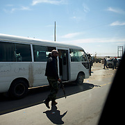 A libyan rebel patrols a checkpoint in a road outside Brega.