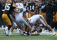 September 3, 2011: Iowa Hawkeyes quarterback James Vandenberg (16) loses his helmet as he his hit by Tennessee Tech Golden Eagles cornerback Will Johnson (4) during the first half of the game between the Tennessee Tech Golden Eagles and the Iowa Hawkeyes at Kinnick Stadium in Iowa City, Iowa on Saturday, September 3, 2011. Iowa defeated Tennessee Tech 34-7 in a game stopped at one point due to lightning and rain.