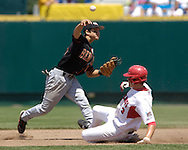 Oregon State shortstop Darwin Barney (L) throws to first for a double play, over Georgia's Ryan Peisel.  Oregon State eliminated Georgia with a 5-3 win at the College World Series at Rosenblatt Stadium in Omaha, Nebraska, June 19, 2006.