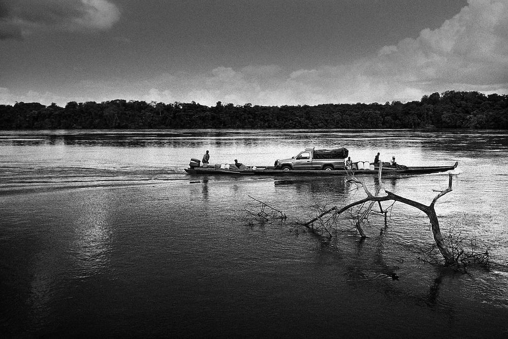Suriname, Camp Metal, maroni.<br /> <br /> Piroguiers bonis (noir marron) sur le Maroni, fleuve frontiere entre le surinam et la guyane francaise sur la totalite de son cours.<br /> <br /> Le Maroni nait dans la region des Tumuc-Humac et des massifs du Mitaraka, a la frontiere bresilienne, de la rencontre de 2 rivieres le Litany et le Marouini qui forment le Lawa au niveau du village d'Antecumpata. <br /> Le Lawa rencontre la Tapanahony a saut Poligoudi a 200 Km de l'estuaire. Ce n'est qu'a cet endroit que le fleuve se nomme veritablement Maroni jusqu'a l'ocean.<br /> Reconnu pour sa navigation difficile, le fleuve est jalonne de sauts aux noms evocateurs &quot; Man Barri &ldquo; le cri de l'homme, &quot; Lesse Dede &quot; qui necessitent beaucoup d'habilite et de courage pour etre franchis en toutes saisons avec un minimum de casse.<br /> Continuellement, les pirogues chargees de fret ravitaillent les communes de l'interieur guyanais.