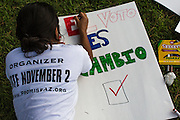 19 JULY 2012 - PHOENIX, AZ:  A woman makes paints a voting sign before an immigrants' rights rally in Phoenix, AZ, Thursday.   PHOTO BY JACK KURTZ